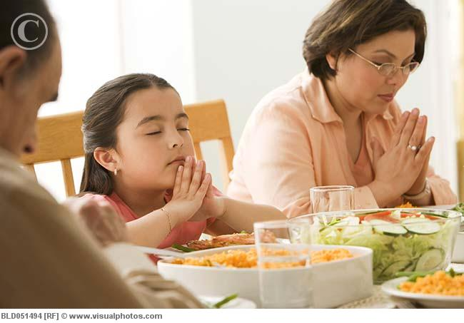Hispanic_family_praying_at_dinner_table_bld051494
